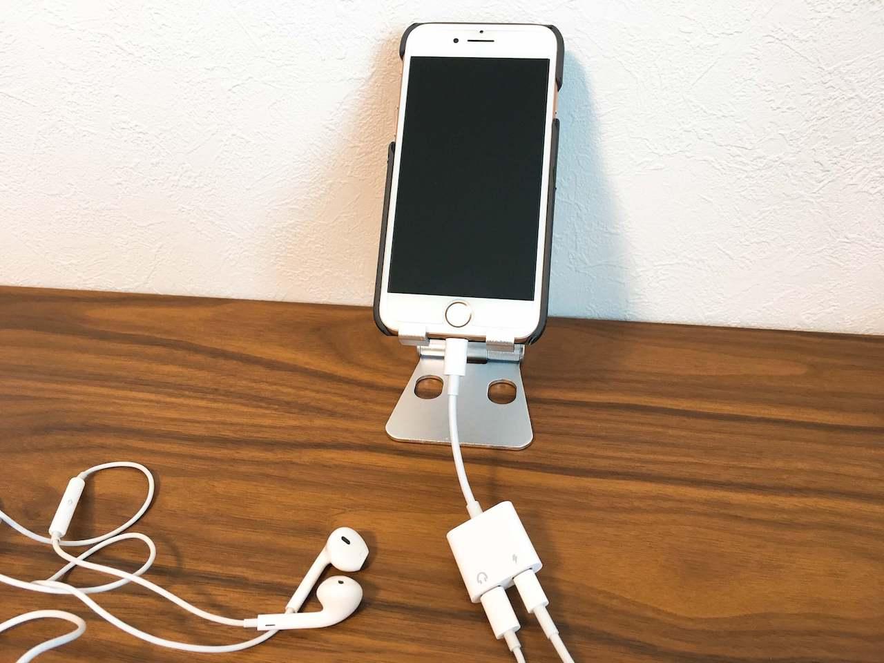 卓上のスマホスタンドにiPhoneを設置。アダプターを使ってイヤホンと充電ケーブルを繋いだ状態の写真です。