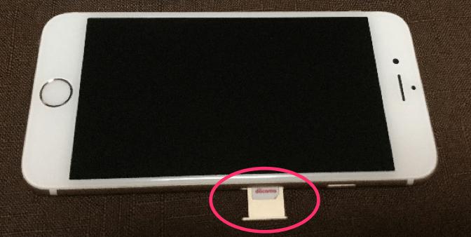 SIMカードをiPhoneに挿しているところです。